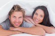 Beautiful couple smiling under the cover