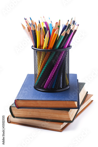 stack of books and colored pencils on white background
