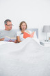 Relaxed couple sitting in bed reading books