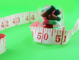 measuring tape and pills for dieting