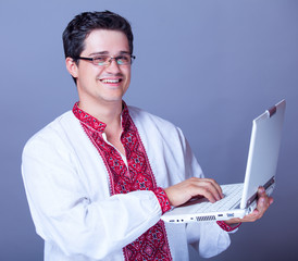 Man in embroidery shirt with laptop
