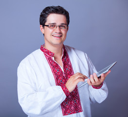 Man in embroidery shirt with tablet