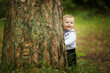 cute beautiful baby hiding behind tree in park