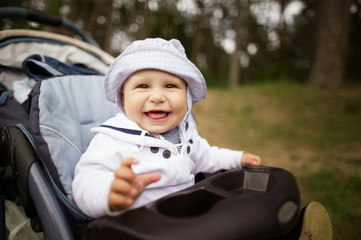 little funny baby portrait in baby carriage