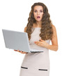 Surprised young woman pointing on laptop