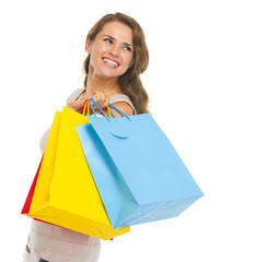 Portrait of happy young woman with shopping bags looking on copy