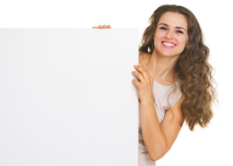 Happy young woman showing blank billboard