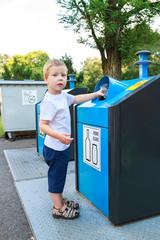 Four year old child putting waste in bin
