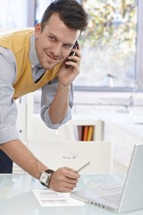 Young man talking on mobile in office, smiling