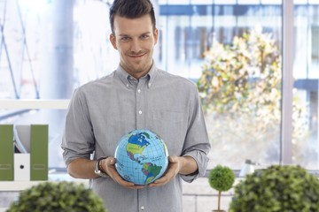 Young man holding globe smiling