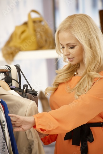 Beautiful woman searching among clothes at store