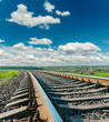 railroad closeup to horizon and deep blue sky with clouds