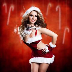 attraktive brünette Weihnachtsfrau pustet Sternchenstaub