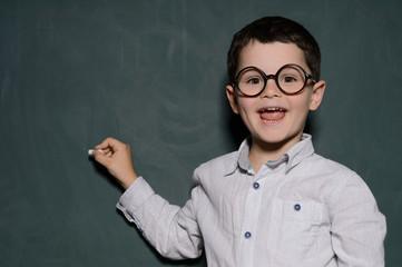 Happy learner. Cheerful little schoolboy in glasses standing nea