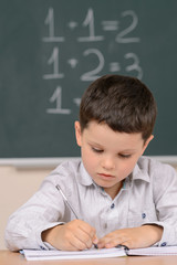Confident little schoolboy. Confident little boy writing somethi
