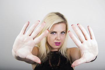 Young woman showing the sign stop with her hands