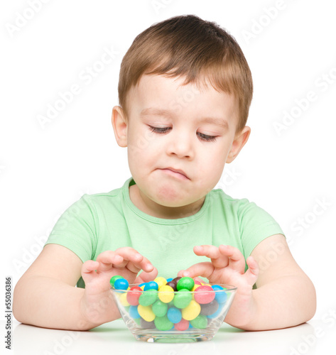 Portrait of a sad little boy with candies