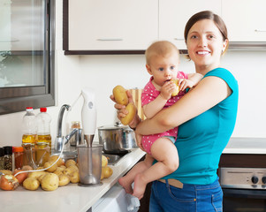 Happy mother and child  with blender in kitchen