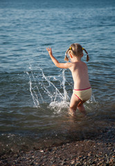 Little girl playing on a pebbly beach