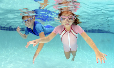 two children swimming underwater in pool