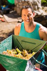 Winzer arbeiten mit Weinpresse