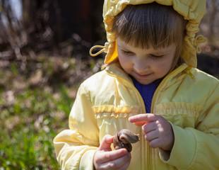Smiling little girl holding garden snail