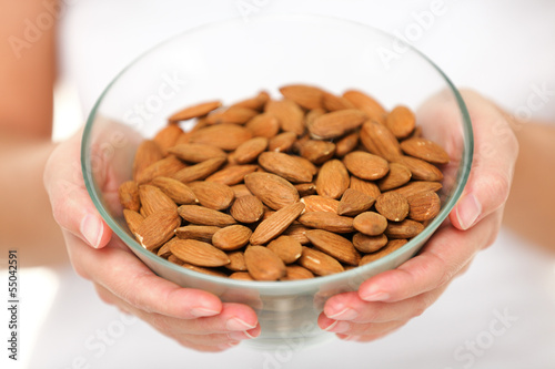 Almonds - woman showing raw almond bowl close up