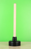 Toilet plunger on green background