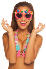 girl celebrating wearing birthday sunglasses on white
