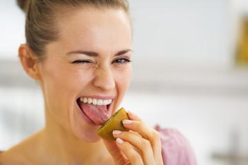 Young woman tasting kiwi