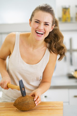 Smiling young woman opening coconut using hammer