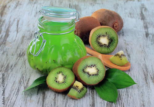 Jar of jam kiwi on wooden table close-up