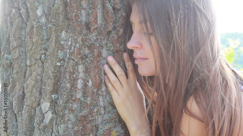 Happy beautiful girl hugging big tree in park