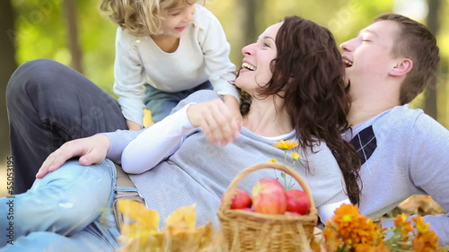 Happy family outdoors in autumn park. Dolly shot