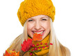 Smiling girl in hat and scarf biting autumn leaf
