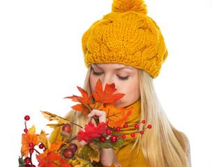 Young woman in hat and scarf smelling autumn bouquet