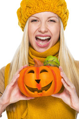 Young woman in hat and scarf with jack-o-lantern