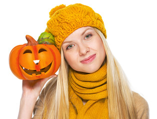 Girl in hat and scarf showing jack-o-lantern