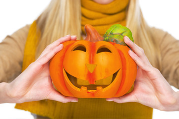 Closeup on jack-o-lantern in hand of young woman