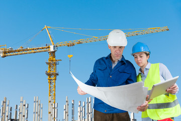 Foreman and engineer with blueprints