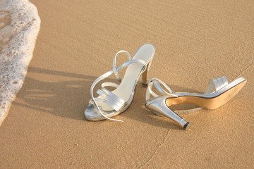 Ladies silver shoes on  a beach