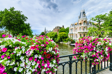 Canal in Amsterdam with flowers on a bridge