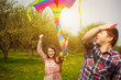 loving couple are fling a kite on a spring meadow