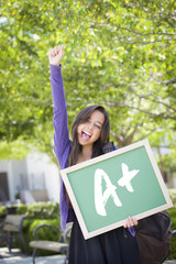 Mixed Race Female Student Holding Chalkboard With A+ Written