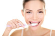 Woman brushing teeth holding toothbrush
