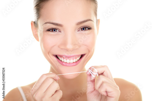 Dental flush - woman flossing teeth smiling