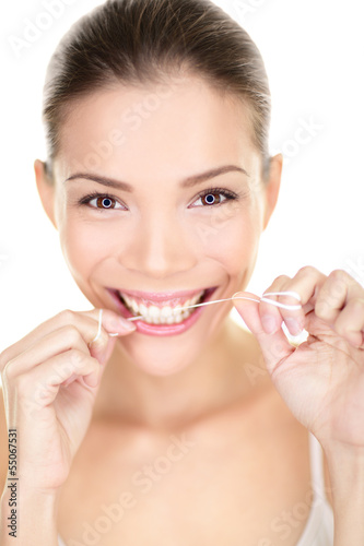 Woman flossing teeth smiling using dental flush