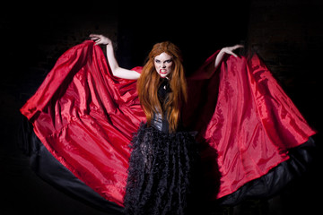 Terrible vampire woman in a red cloak