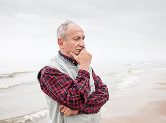 Thoughtful elderly man standing on the beach