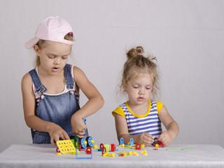 Двое детей играют в конструктор